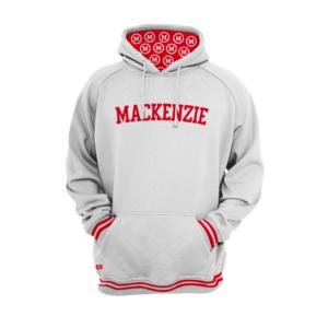 moletom branco com duas listras vermelhas na área da cintura e das mangas com mackenzie escrito em vermelho no peito. A parte de dentro da touca tem fundo vermelho e logomarca do Mackenzie em branco repetida por todo o fundo
